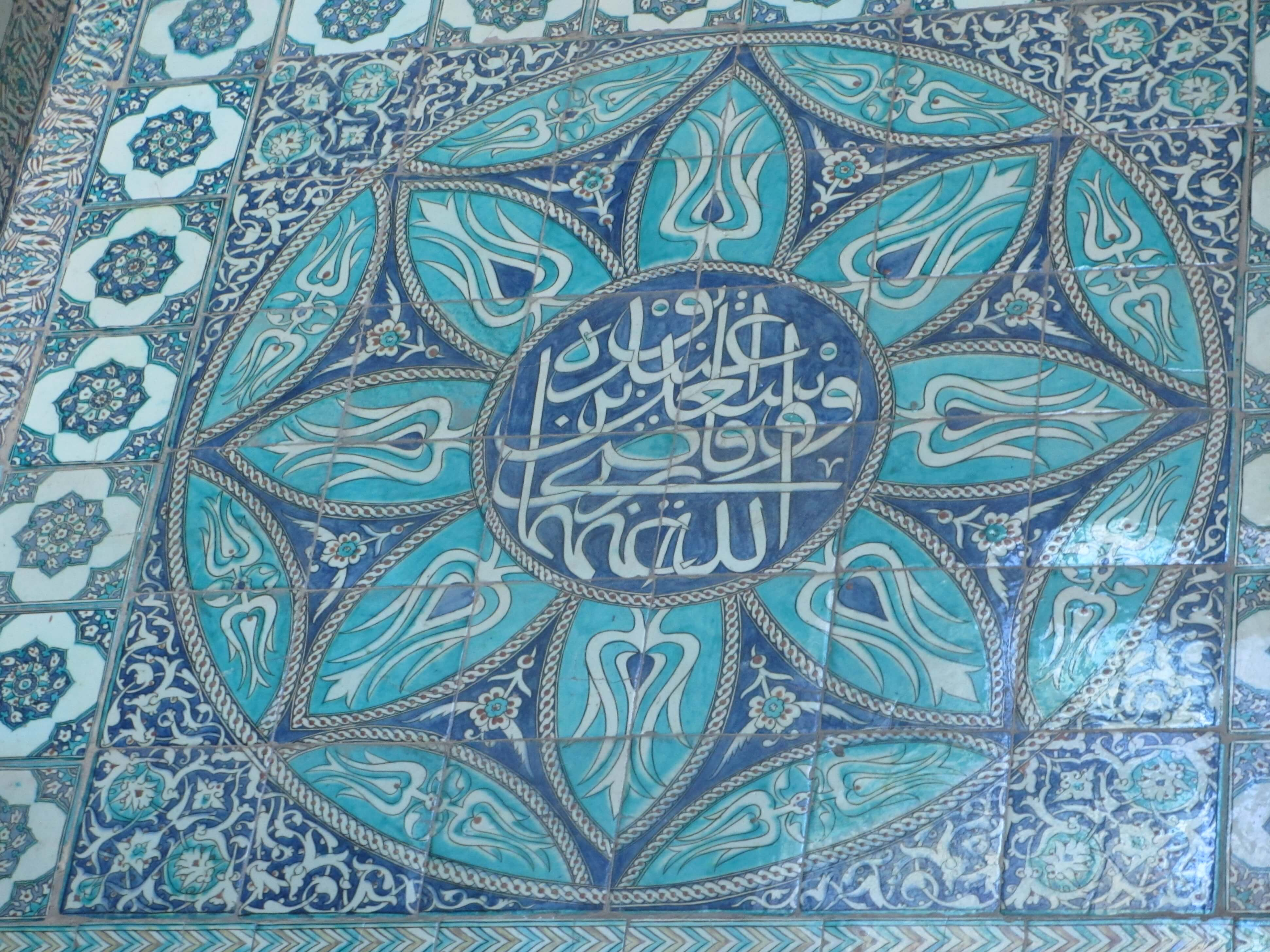 Blue Iznik tiles in a flower pattern, with Islamic writing in the centre