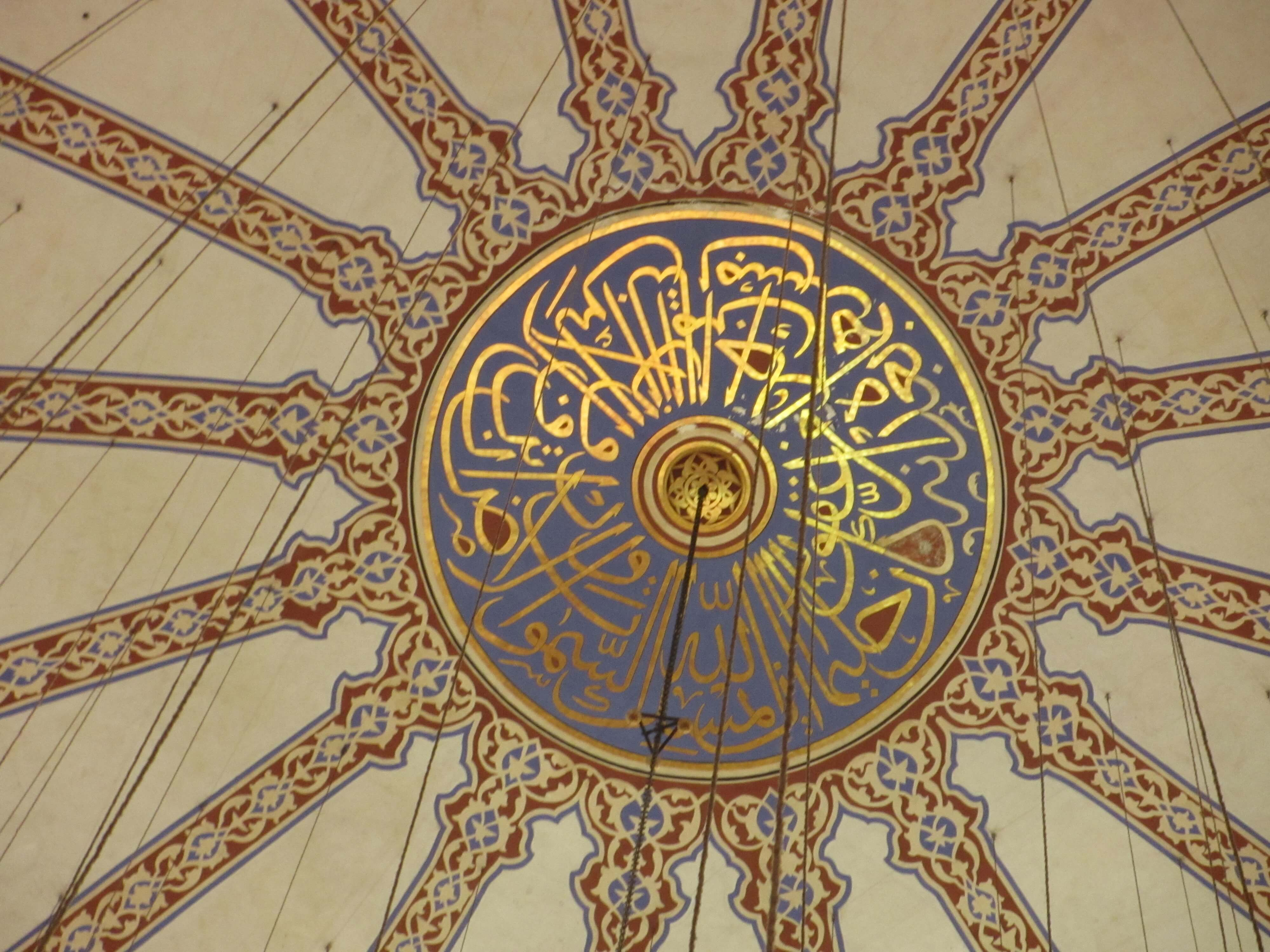 Islamic text in a blue circle surrounded by other coloured decoration