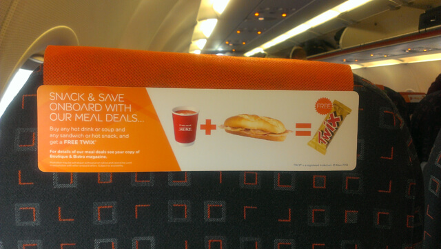 cardboard advertising for snacks on the back of the plane seats