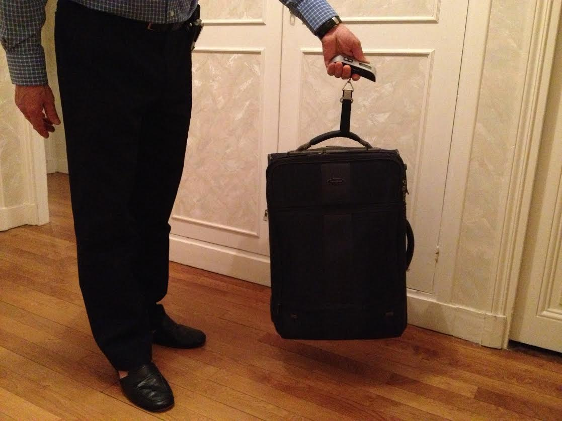 luggage scales, suitcase being held by a man