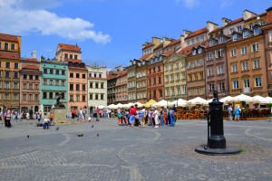 old town square with old colourful building, umbrellas and people standing