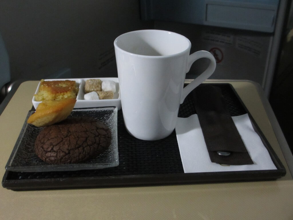 mug of coffee with chocolate cookie and madeleine