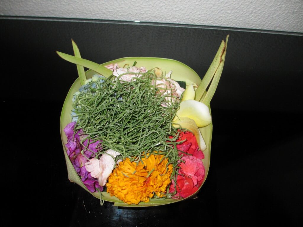 banana leaves folded into a bowl with flowers and Hindu offerings