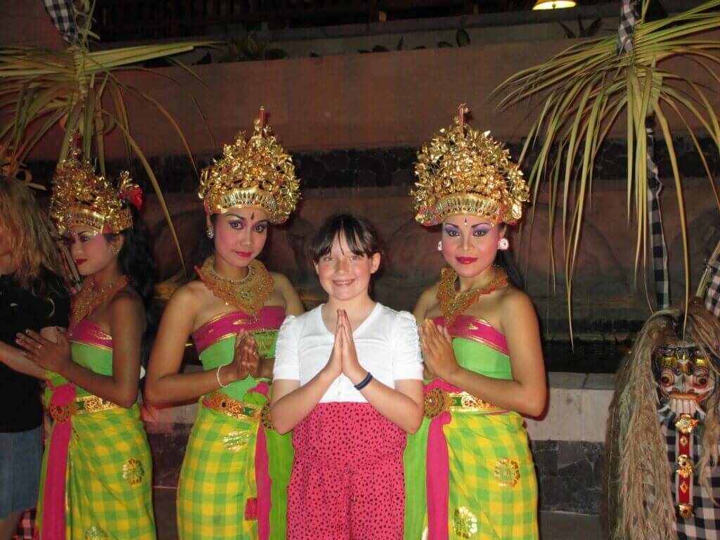 two Balinese dancers in green and yellow costumes with head pieces, young girl