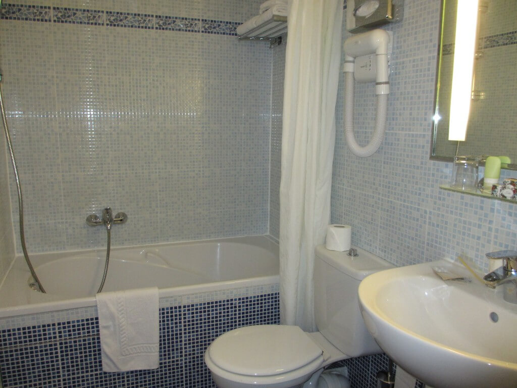 bathroom with square blue tiles and white bath, toilet and basin