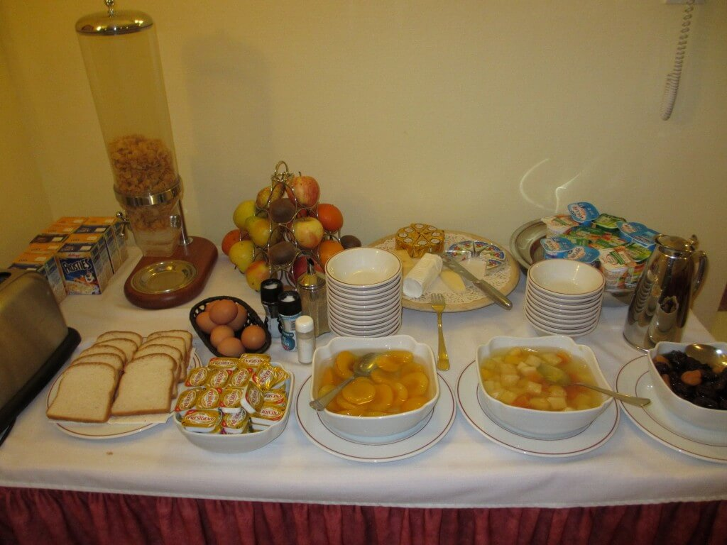 white table cloth, white bowls with fruit, cereal and jams