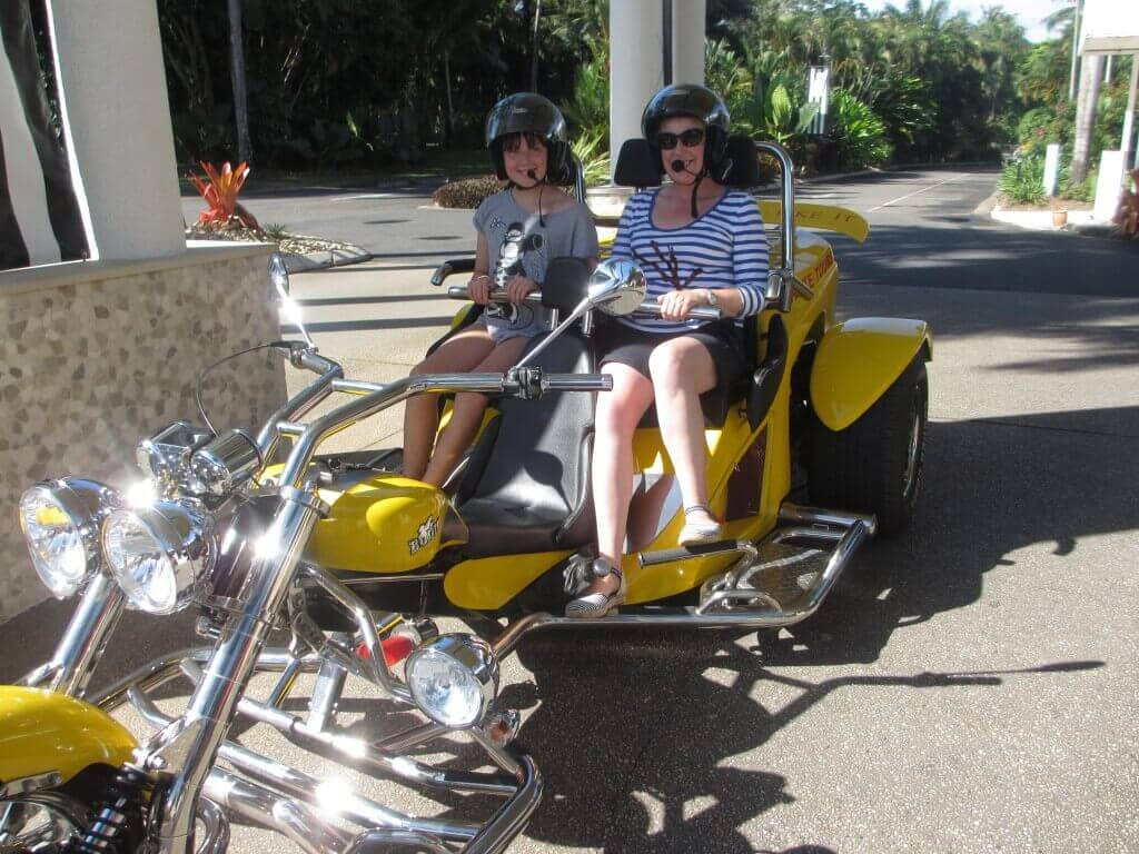 yellow three wheel motor cycle with two women sitting on it