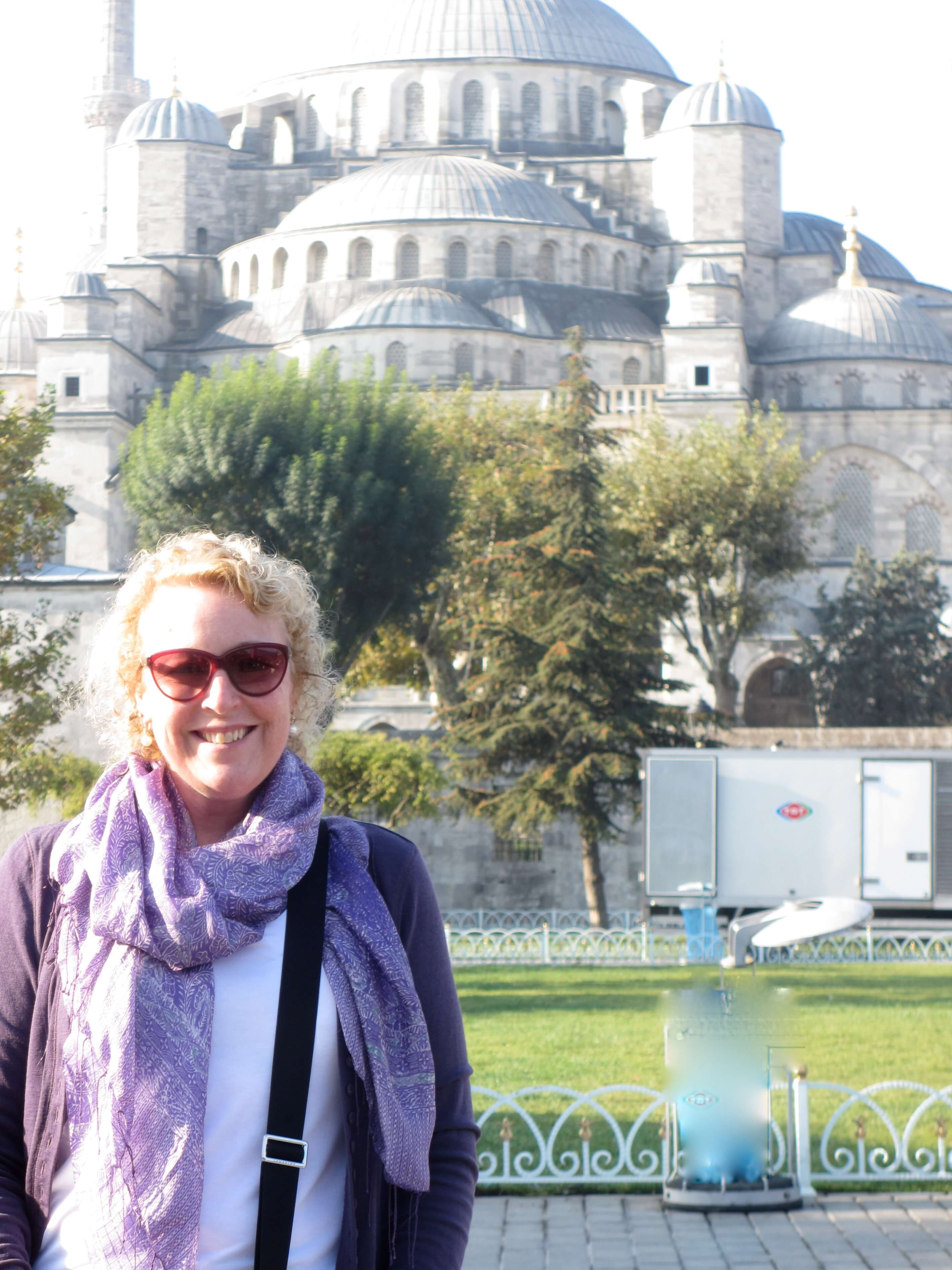 Jo Karnaghan wearing a purple cardigan and purple scarf standing in front of the Blue Mosque in Istanbul