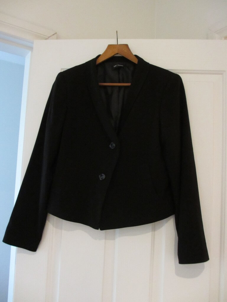 cropped black jacket on a hanger