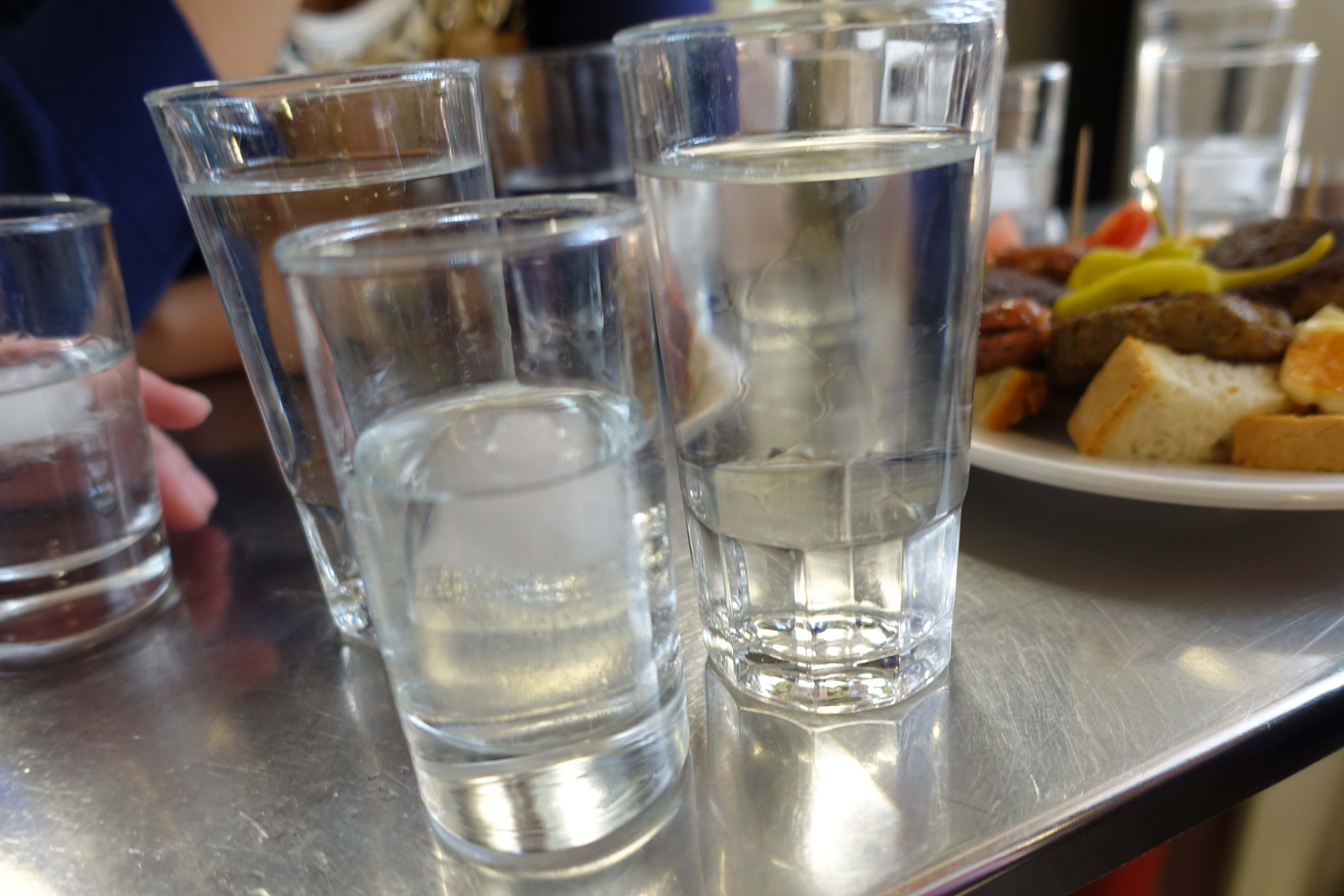 glasses of tsipouro and water at a cafe in Athens fish market