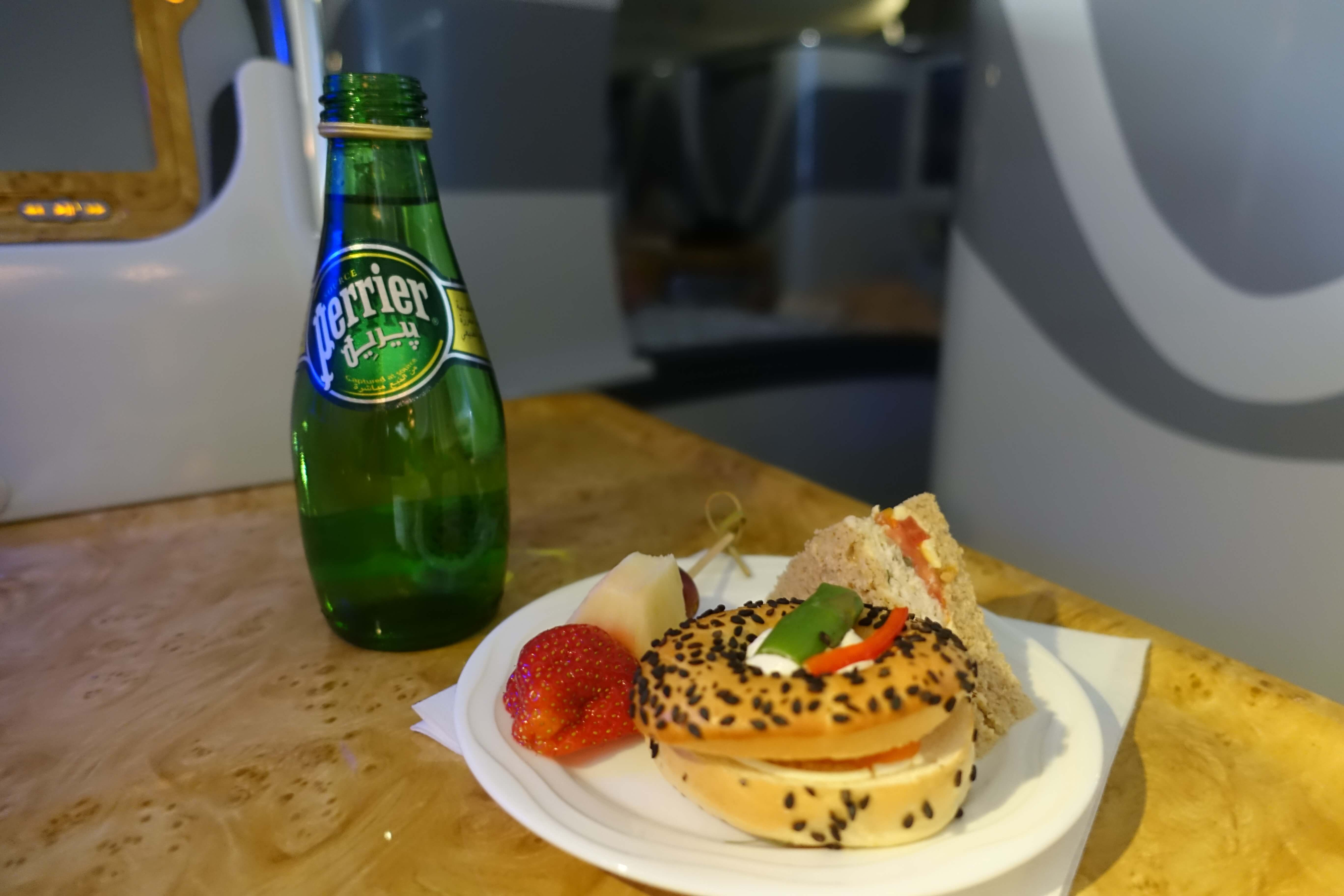 plate of bagel, sandwich and bottle of Perrier