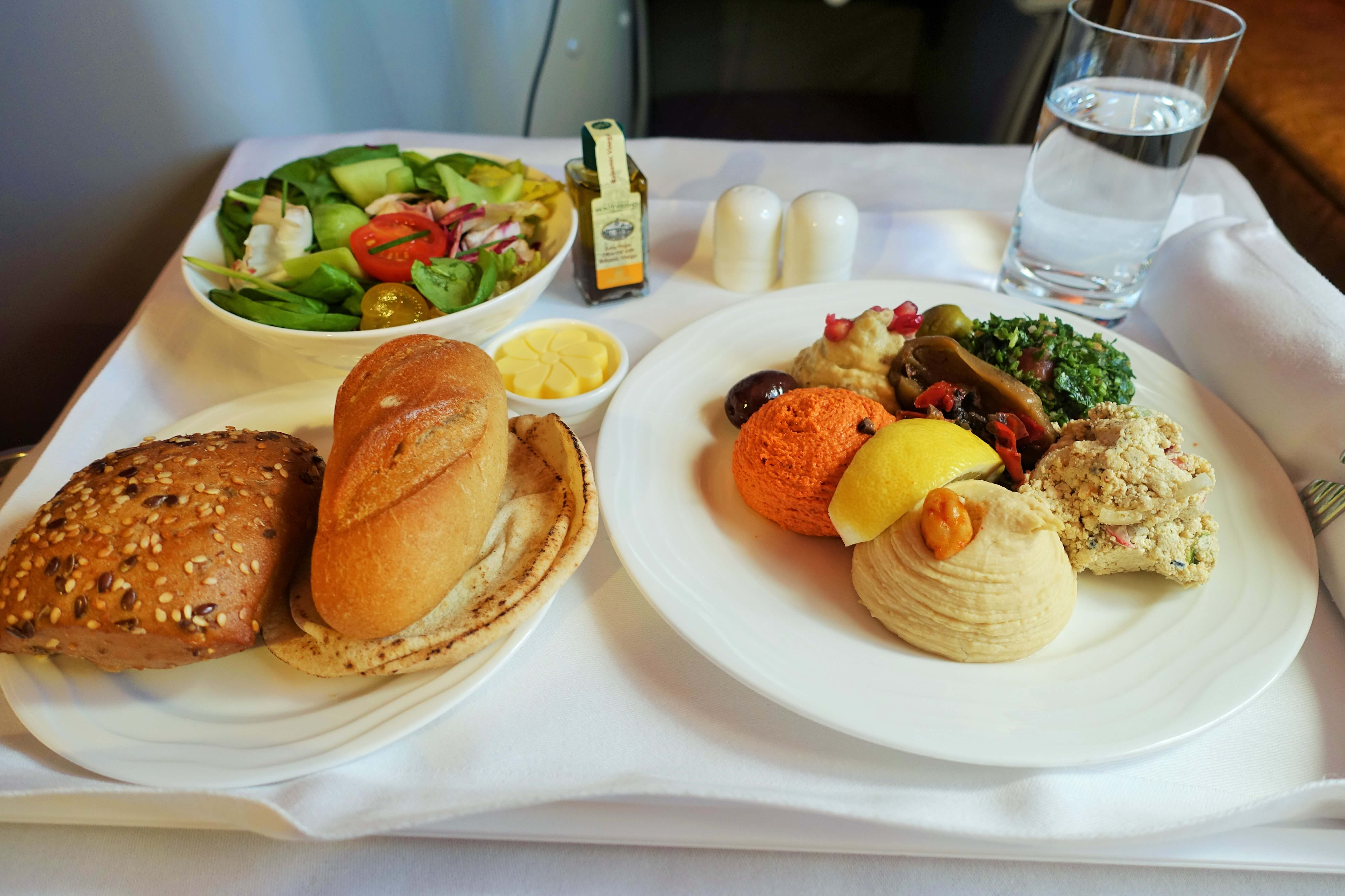 Emirates business meal, meze plate, salad, bread rolls on tray