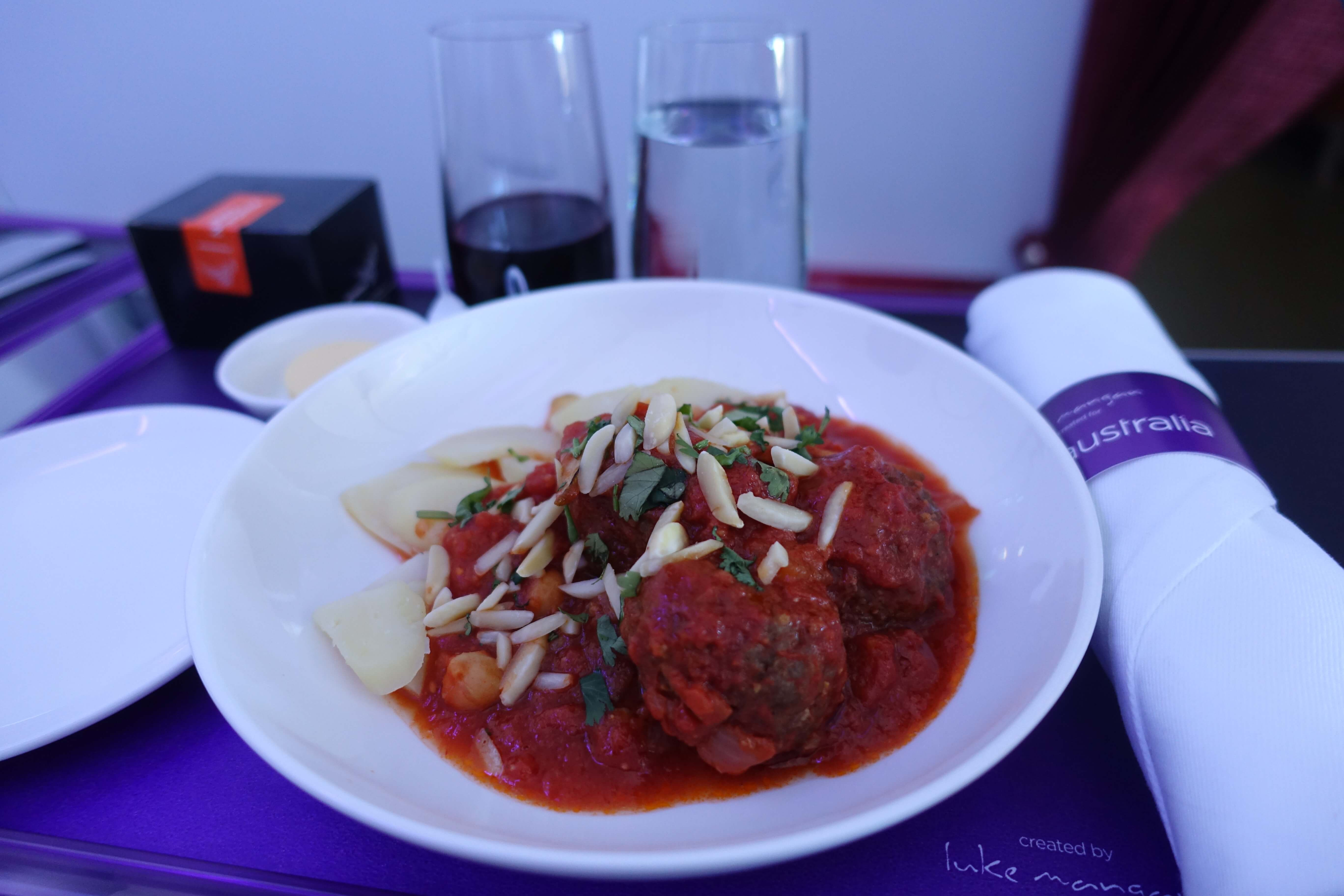plate of lamb meatballs with tomato sauce on a white plate, served on ...