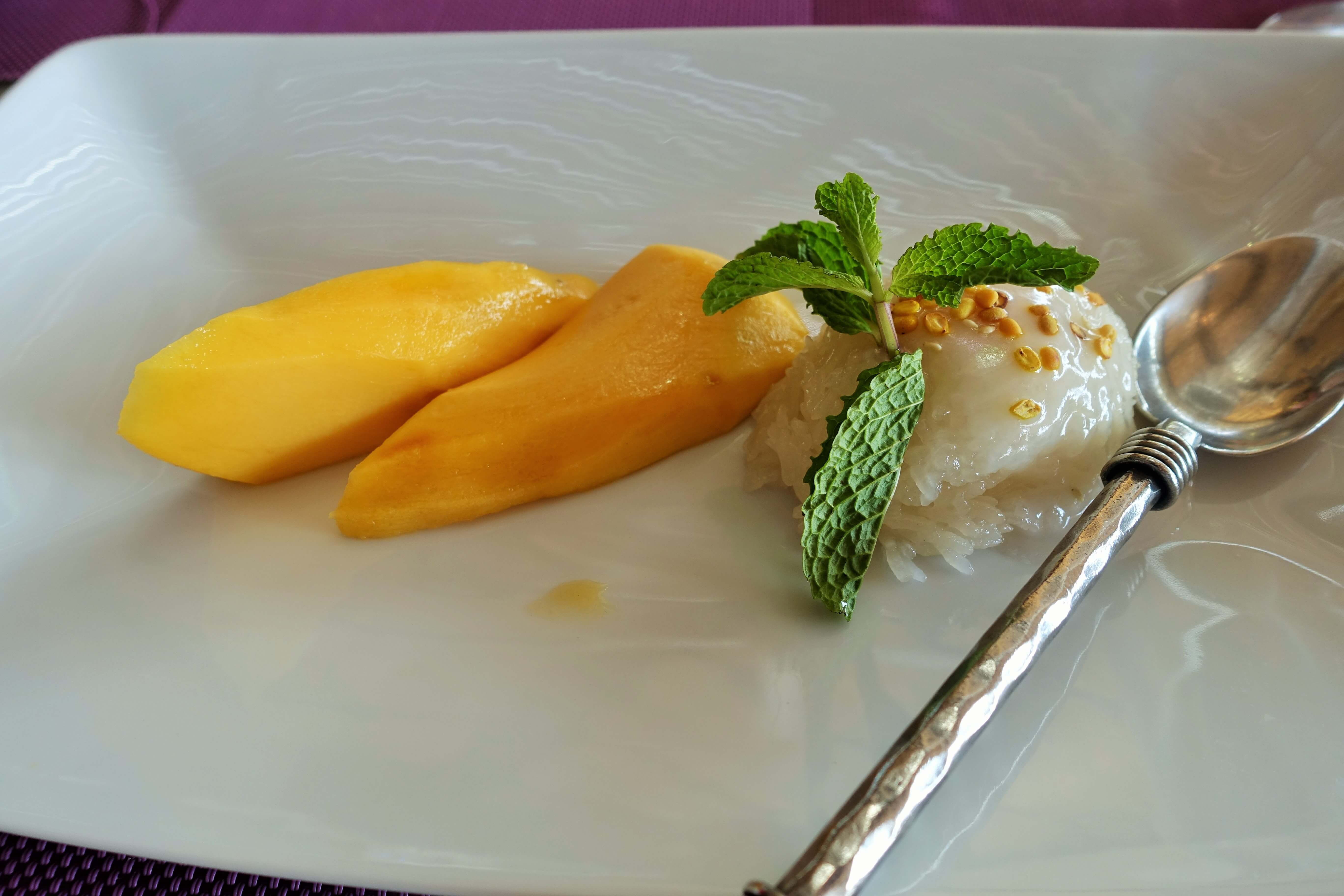 mango cheeks with sticky rice and a silver spoon