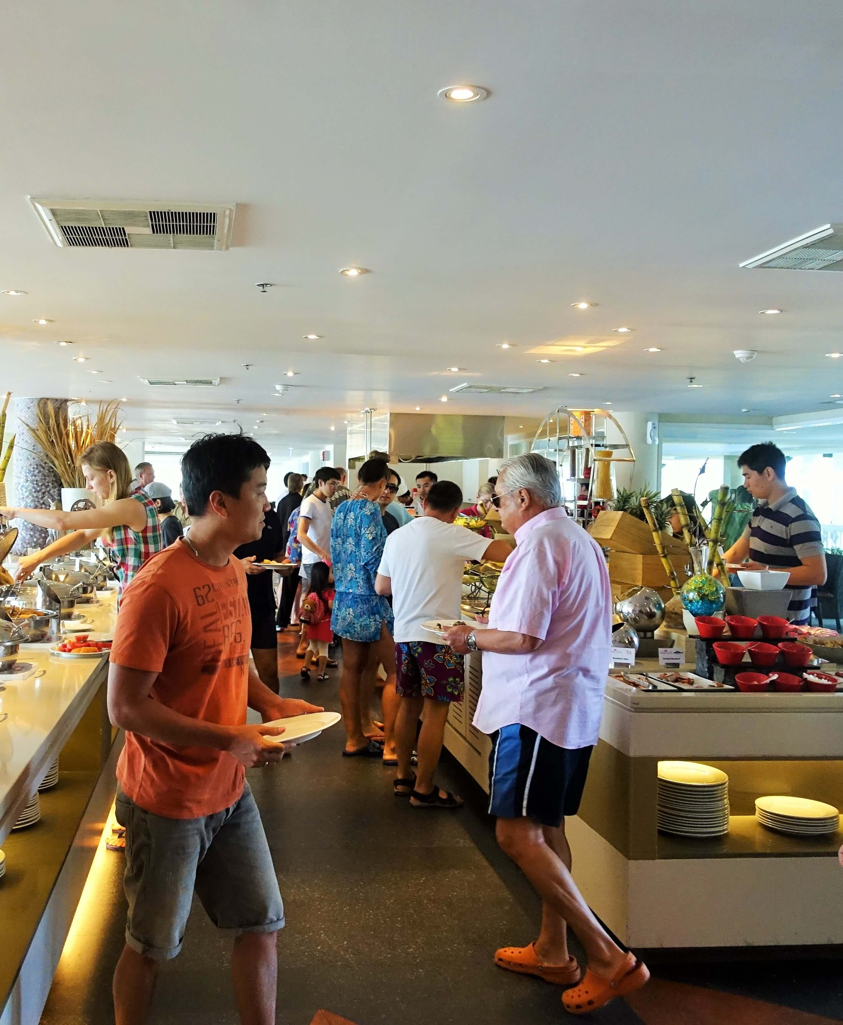 crowds of people round a breakfast buffet