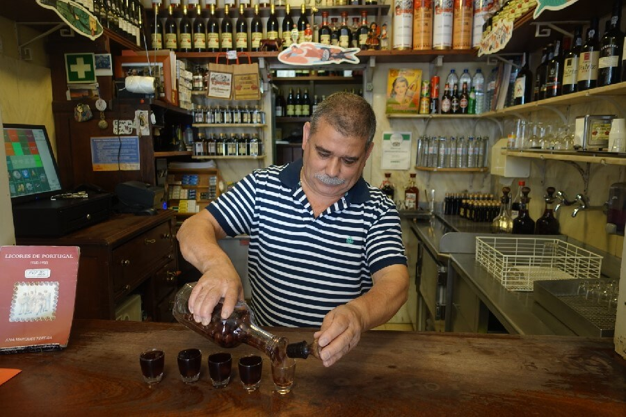 The best food walk in Lisbon with Culinary Backstreets pouring ginjinha in the Baixa
