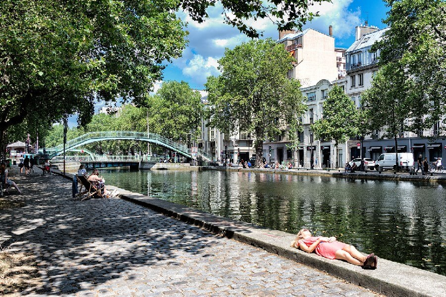Girl lying in the sun Canal St Martin Paris France