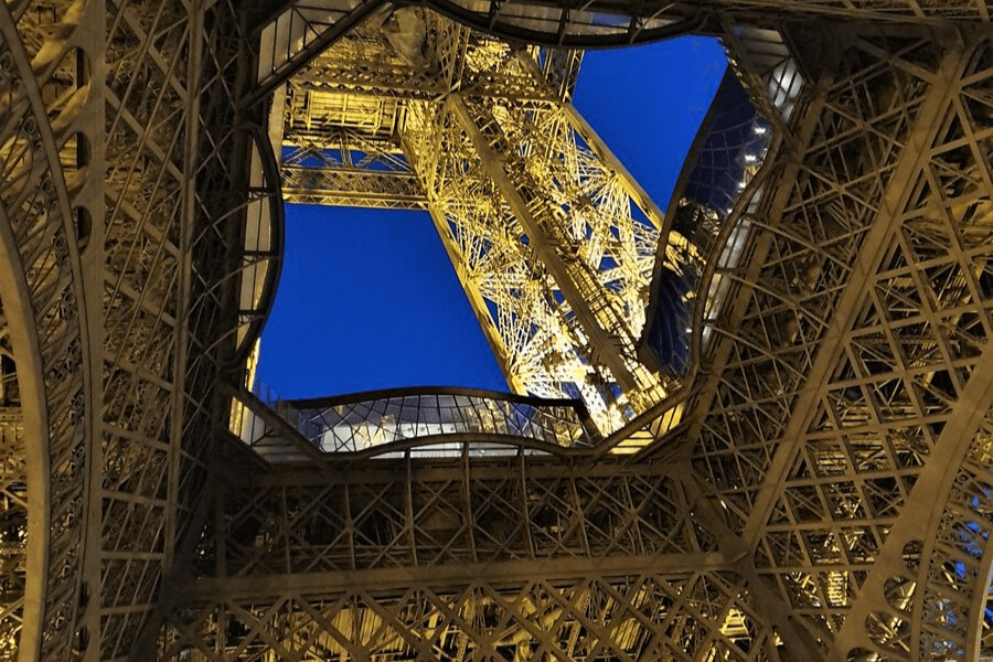Looking up into the Eiffel Tower from below at night