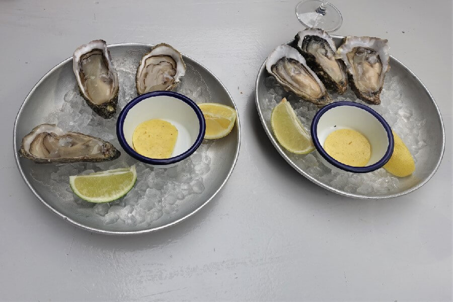 plates of French oysters served with lemon. In the Marais, Paris