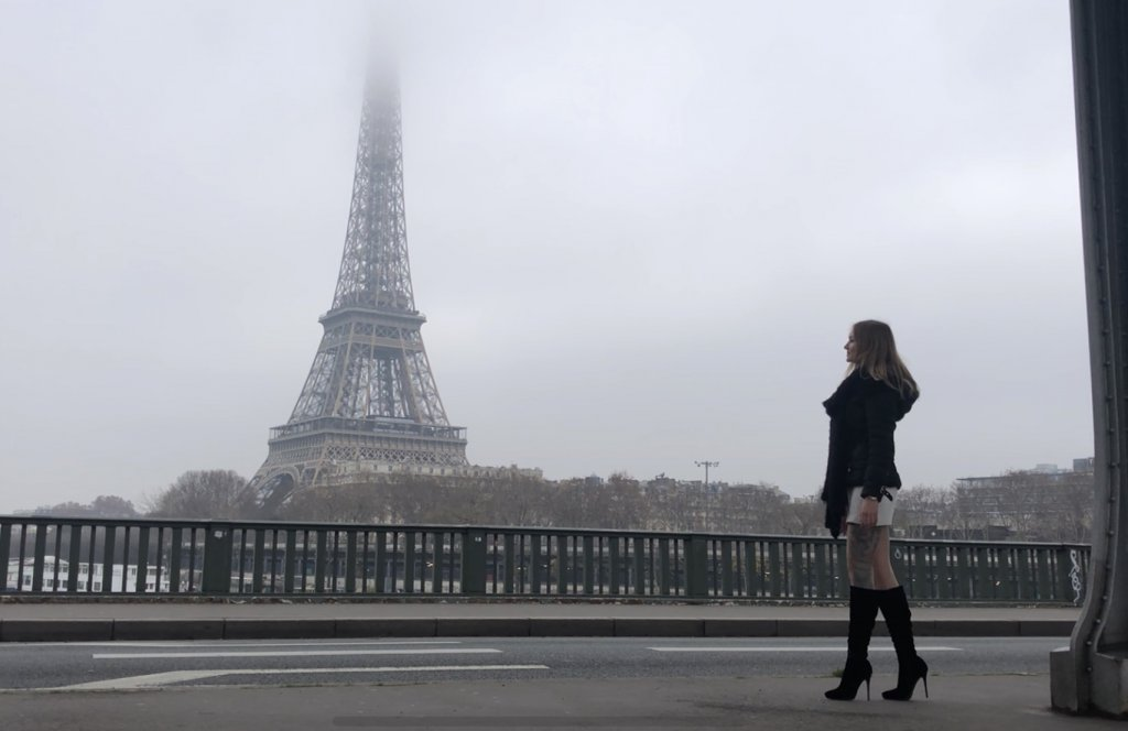young woman standing in front of the Eiffel Tower, Eiffel Tower in winter, A budget guide to Paris